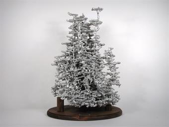A very large aluminum fire ant colony cast displayed on a wood base.